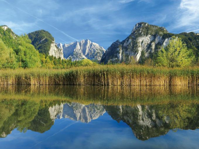 Berglandschaft spiegelt sich in einem See im Nationalpark Gesäuse in der Nähe vom JUFA Hotel Schloss Röthelstein. Der Ort für erholsamen Familienurlaub und einen unvergesslichen Winter- und Wanderurlaub.