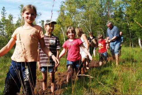 Kinder stapfen durch das Moor vom Naturpark Zirbitzkogel-Grebenzen in Murtal-Spielberg in der Nähe vom JUFA Hotel Murau. Der Ort für erholsamen Familienurlaub und einen unvergesslichen Winter- und Wanderurlaub.