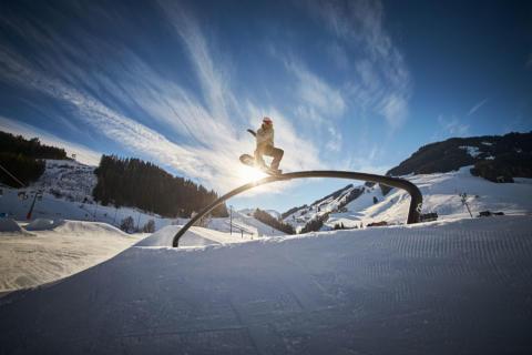 Sie sehen einen Skifahrer im Nightpark in Saalbach auf einem Hindernis. JUFA Hotels bietet kinderfreundlichen und erlebnisreichen Urlaub für die ganze Familie.
