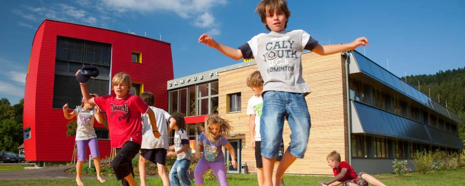 Kinder hüpfen auf Hüpfburg im Outdoorspielbereich vom JUFA Hotel Bleiburg – Sport-Resort. Der Ort für erholsamen Familienurlaub und einen unvergesslichen Winter- und Wanderurlaub.