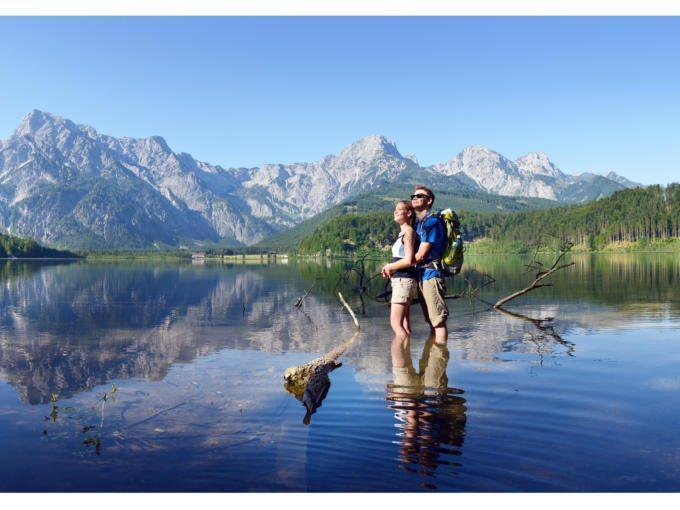 Ein junges Paar steht umarmend im Sommer im Almsee in Oberösterreich. JUFA Hotels bietet Ihnen den Ort für erlebnisreichen Natururlaub für die ganze Familie.