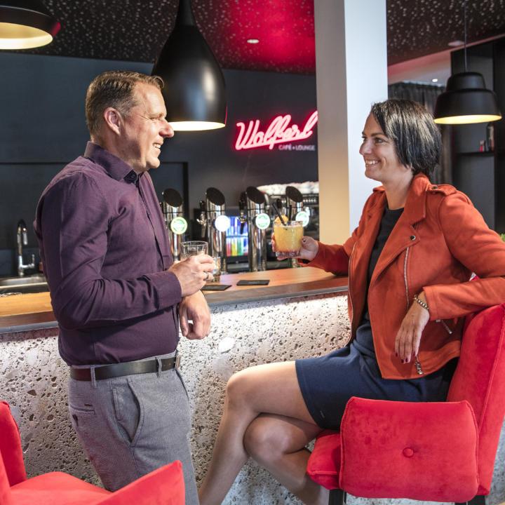 Sie sehen ein Paar mit Getränken an der Bar im JUFA Hotel Salzburg City. Der Ort für erholsamen Familienurlaub und einen unvergesslichen Winter- und Wanderurlaub.