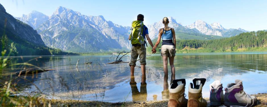 Ein junges Paar steht im Sommer händehaltend im Almsee im Almtal. JUFA Hotels bietet Ihnen den Ort für erlebnisreichen Natururlaub für die ganze Familie.