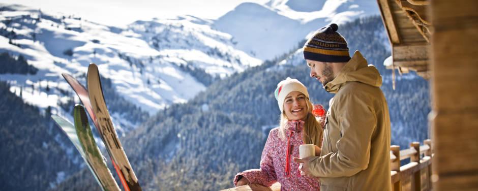 Sie sehen ein Paar rastend auf Hüttenbalkon im Skicircus Saalbach Hinterklemm. JUFA Hotels bietet erholsamen Familienurlaub und einen unvergesslichen Winterurlaub.