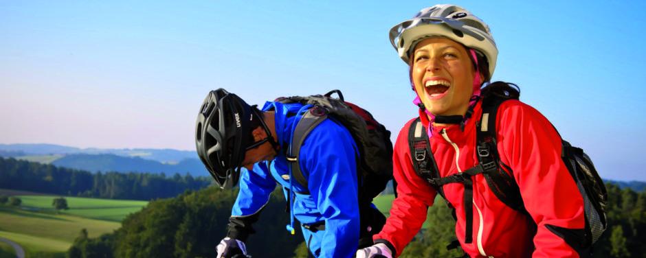 Paar hat Spaß beim Mountainbiken. JUFA Hotels bieten erholsamen Familienurlaub und einen unvergesslichen Winter- und Wanderurlaub.