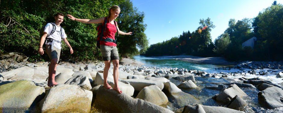 Ein junges Paar balanciert im Sommer über große Steine im Flussbett des Almflusses in Oberösterreich. JUFA Hotels bietet Ihnen den Ort für erlebnisreichen Natururlaub für die ganze Familie.