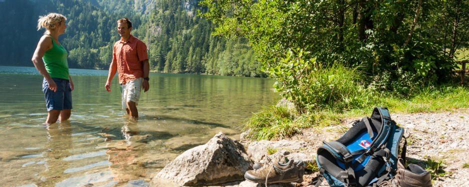 Paar macht Pause beim Wandern und erfrischt sich im Gleinkersee in Oberösterreich. JUFA Hotels bietet tollen Sommerurlaub an schönen Seen für die ganze Familie.
