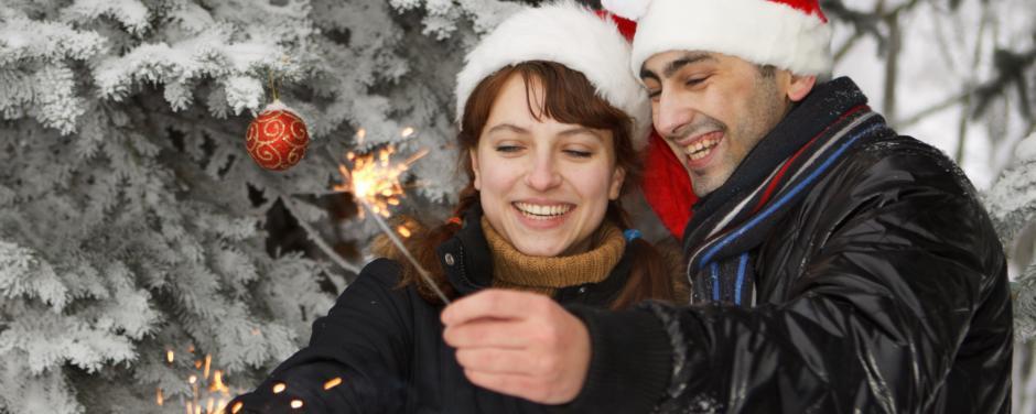 Ein Paar mit Weihnachtsmannmützen steht vor verschneiten Bäumen und hält Spritzkerzen. JUFA Hotels bietet erholsamen Familienurlaub und einen unvergesslichen Winterurlaub.