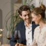 Sie sehen ein Paar mit Wein im EventArium am JUFA Hotel Neutal – Landerlebnis. Der Ort für erlebnisreichen Natururlaub für die ganze Familie.