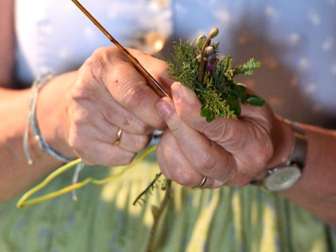 Sie sehen Damenhände beim Fertigen der traditionellen Palmbuschen zu Ostern