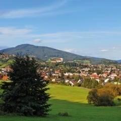 Sie sehen ein Panorama von Weiz mit Hügeln. JUFA Hotels bietet erholsamen Familienurlaub und einen unvergesslichen Winter- und Wanderurlaub.