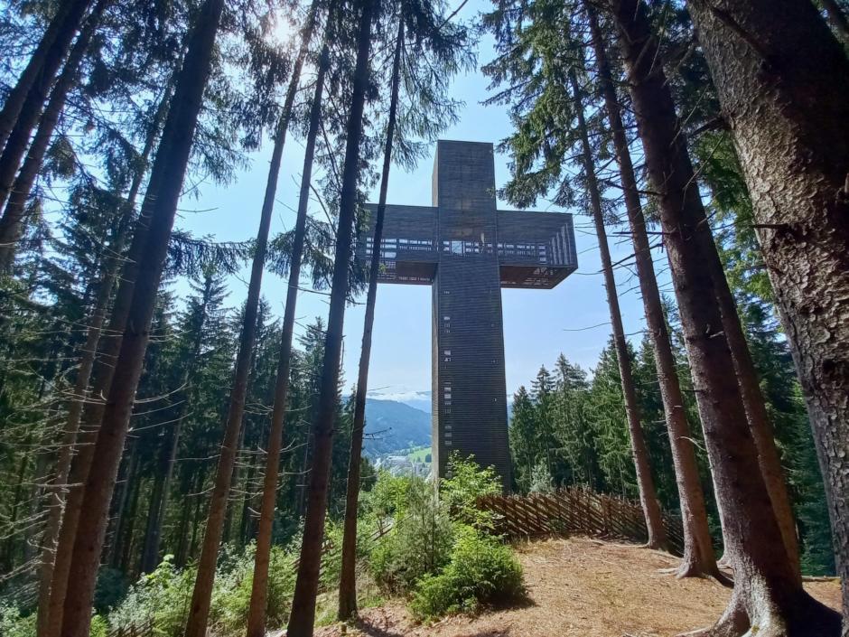 Sie sehen das Pilgerkreuz umgeben von Bäumen.