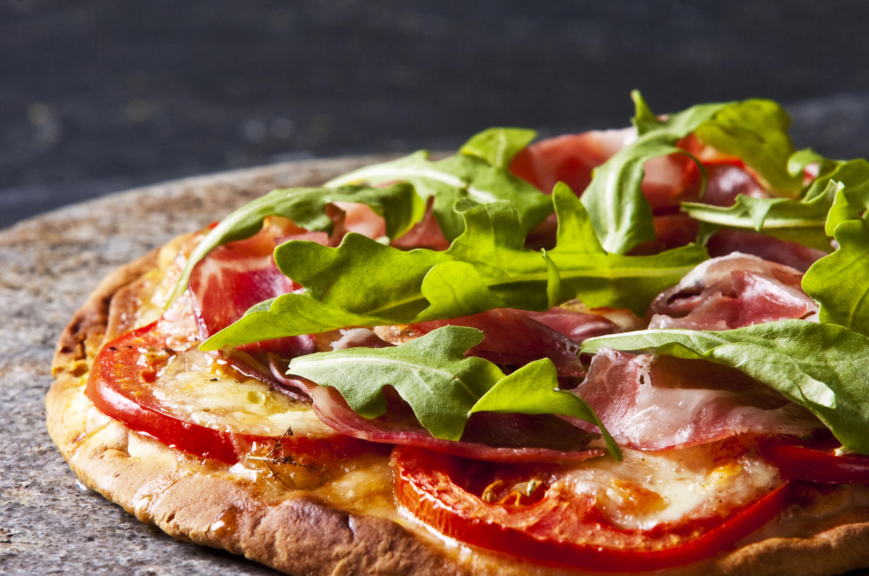 Sie sehen eine ganze Pizza mit Rucola, Schinken und Tomaten