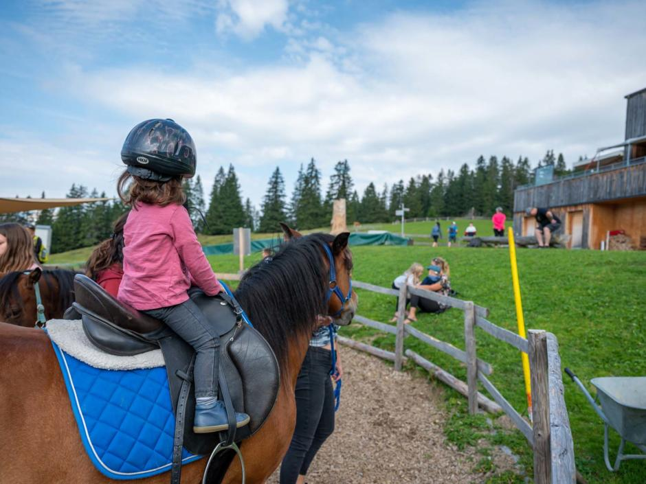 Sie sehen ein Mädchen beim Ponyreiten am Tipiberg bei der Falba Stuba. Die JUFA Hotels bieten erholsamen Urlaub im Winter wie im Sommer.
