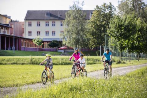 Sie sehen eine Familie beim Rad fahren und im Hintergrund das JUFA Hotel Waldviertel. JUFA Hotels bietet Ihnen den Ort für erlebnisreichen Natururlaub für die ganze Familie.