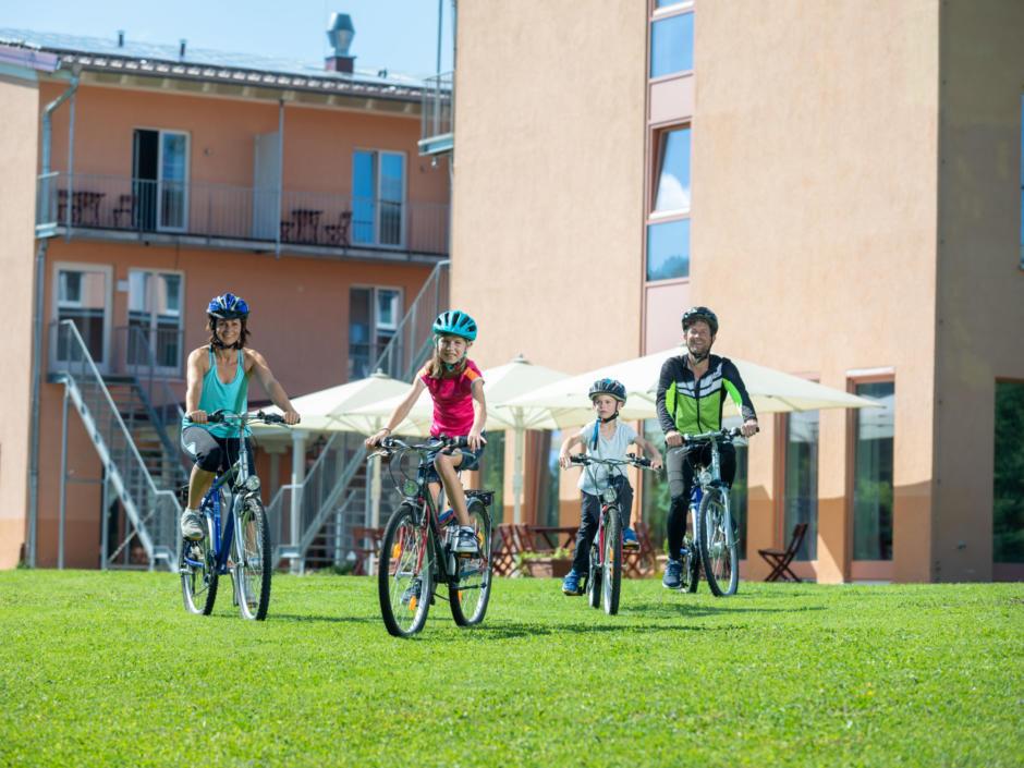 Sie sehen eine Familie im Radurlaub beim Start der Tour mit Leihrädern im JUFA Kempten. Der Ort für kinderfreundlichen und erlebnisreichen Urlaub für die ganze Familie.