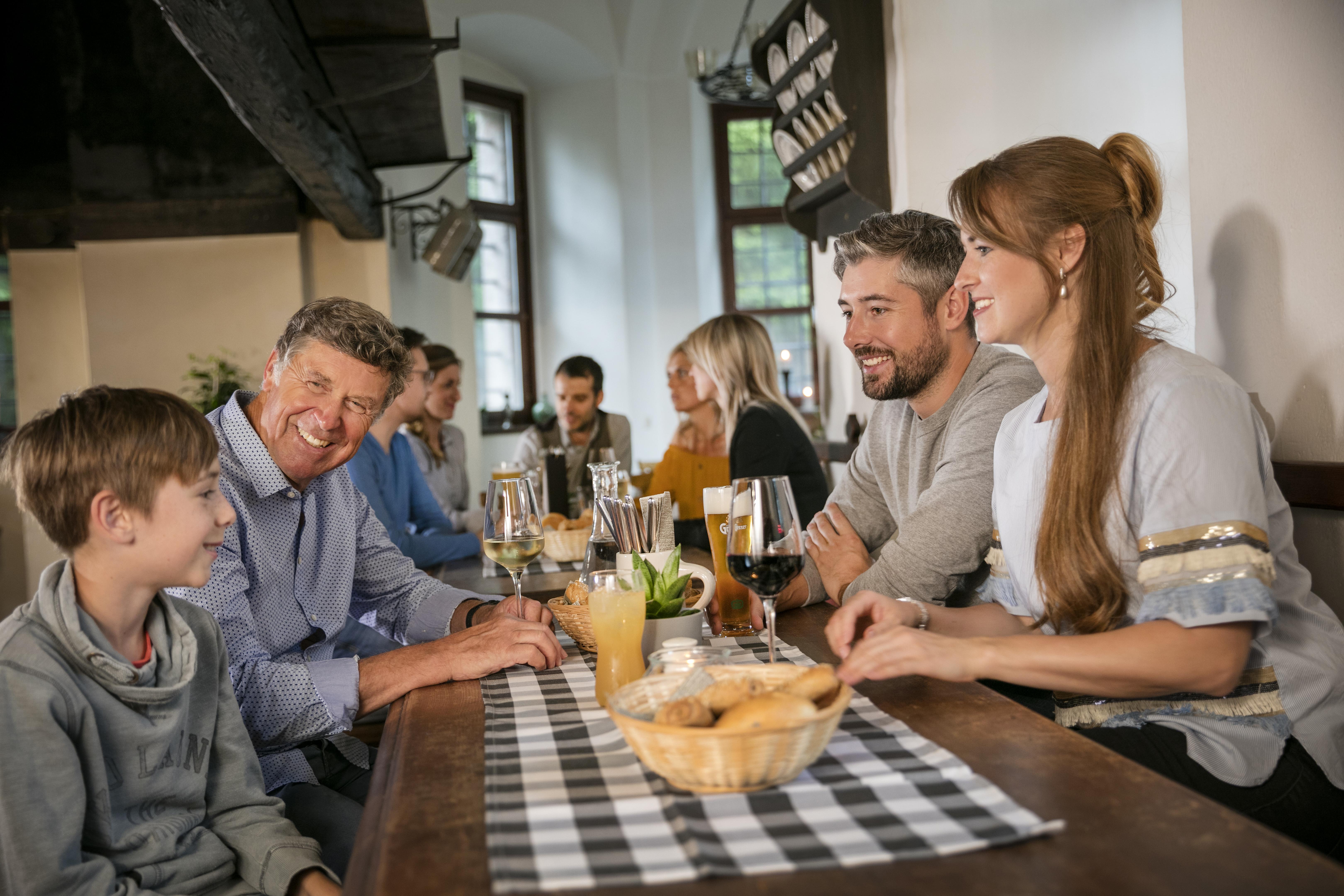 Sie sehen Gäste in der Rauchkuchl im JUFA Hotel Schloss Röthelstein/Admont*** beim Essen sitzen. Der Ort für märchenhafte Hochzeiten und erfolgreiche und kreative Seminare.