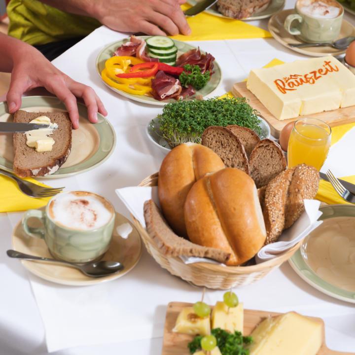 Sie sehen das reichhaltige Rauszeit-Frühstück im JUFA Hotel Maria Lankowitz mit frischem Brot. JUFA Hotels bietet erholsamen Familienurlaub und einen unvergesslichen Winter- und Wanderurlaub.