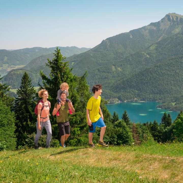 Familie beim Wandern auf das Zwölferhorn im Salzkammergut. JUFA Hotels bietet erholsamen Familienurlaub und einen unvergesslichen Winter- und Wanderurlaub.