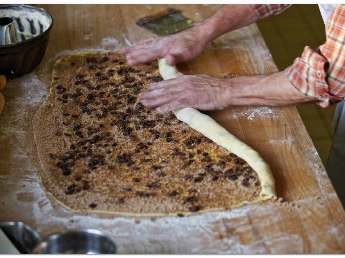 Sie sehen das Einrollen des Germteiges - fertig gebacken genießt man den süßen Kärntner Reindling.