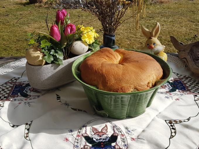 Sie sehen den fertig gebackenen Oster-Reindling mit Osterdeko und Frühlingsgrüßen.