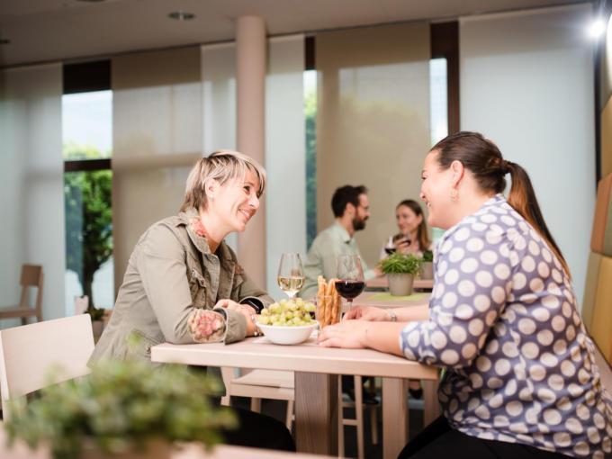 Sie sehen Frauen im Restaurant im JUFA Hotel Graz-Süd mit einem Weinglas. Der Ort für erlebnisreichen Städtetrip für die ganze Familie und der ideale Platz für Ihr Seminar.