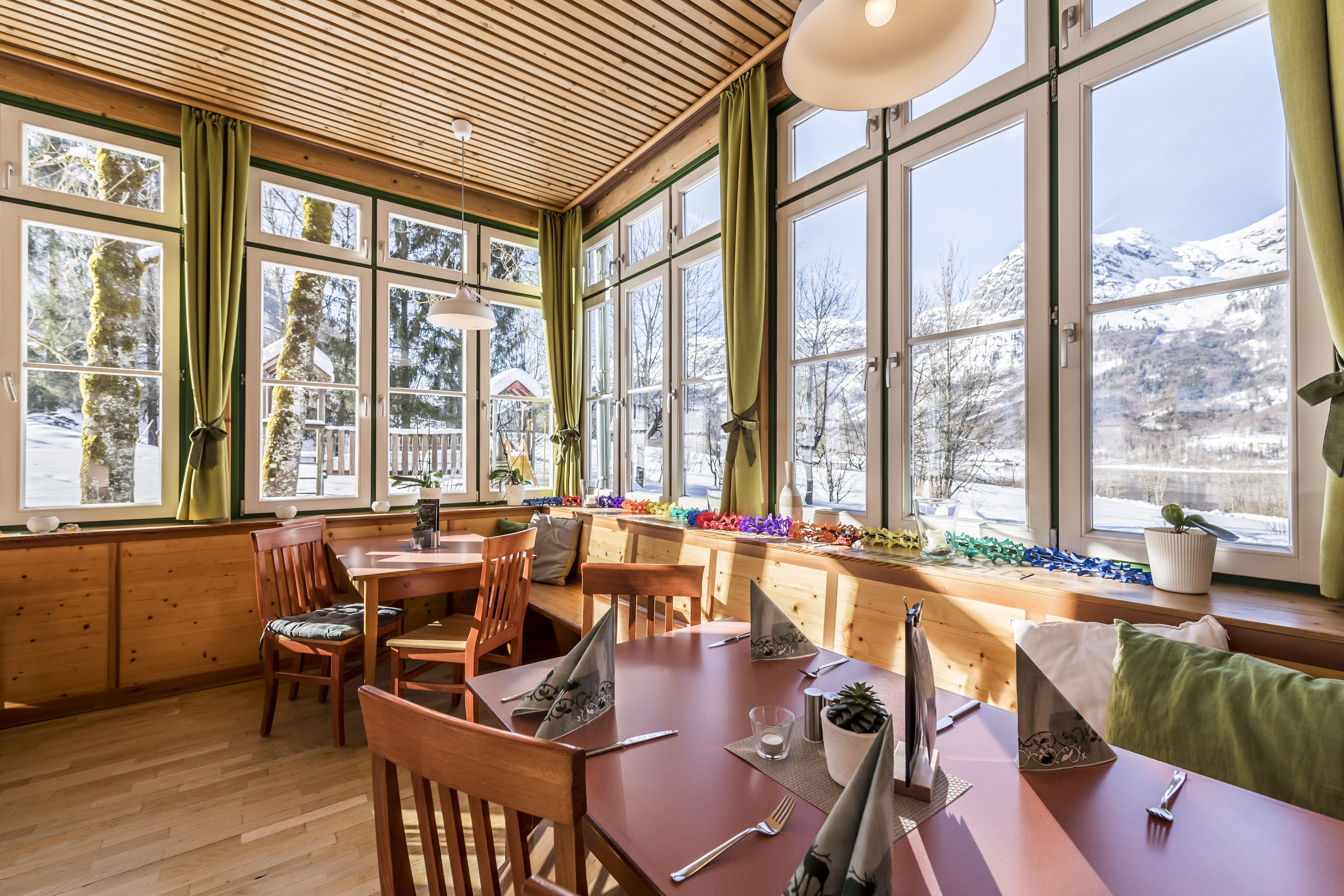 Sie sehen das Restaurant im JUFA Hotel Grundlsee*** mit Tischdeko. JUFA Hotels bietet erholsamen Familienurlaub und einen unvergesslichen Winterurlaub.