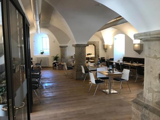 Sie sehen das Restaurant mit Tischen und Stühlen im JUFA Hotel Kronach – Festung Rosenberg*** . Der Ort für kinderfreundlichen und erlebnisreichen Urlaub für die ganze Familie.