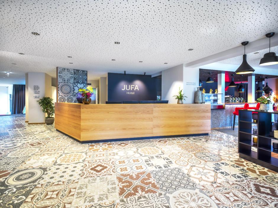 Sie sehen eine Rezeption im JUFA Hotel Salzburg City. Der Ort für erholsamen Familienurlaub und einen unvergesslichen Winter- und Wanderurlaub.