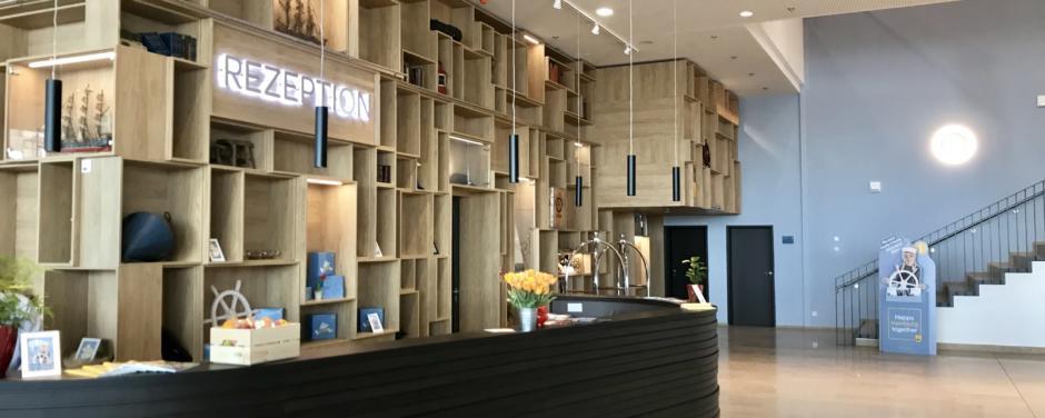 Sie sehen die Rezeption im JUFA Hotel Hamburg HafenCity****. Der Ort für erlebnisreichen Städtetrip für die ganze Familie und den idealen Platz für Ihr Seminar.