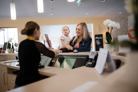 Sie sehen die Rezeption im JUFA Hotel Stubenbergsee mit einer Mutter und ihrem Kind. Der Ort für erholsamen Familienurlaub und einen unvergesslichen Winterurlaub.