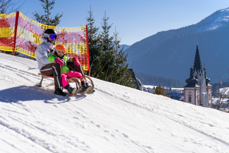 Sie sehen einen Vater mit Kind beim Rodeln auf der Mariazeller Bürgeralpe. JUFA Hotels bietet erholsamen Familienurlaub und einen unvergesslichen Winterurlaub.