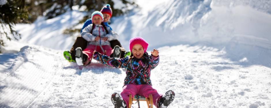 Sie sehen eine Familie mit Schlitten im Winter beim rodeln auf der Planneralm. JUFA Hotels bietet erholsamen Familienurlaub und einen unvergesslichen Winterurlaub.