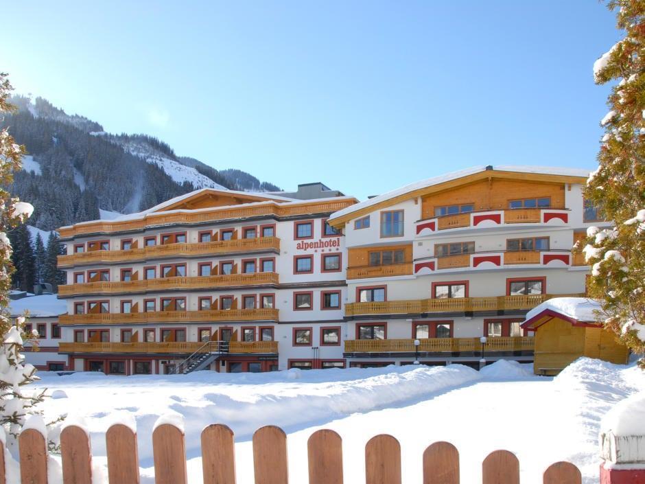 Sie sehen die Rückansicht des JUFA Alpenhotel Saalbach im Winter. JUFA Hotels bietet erholsamen Familienurlaub und einen unvergesslichen Winterurlaub.