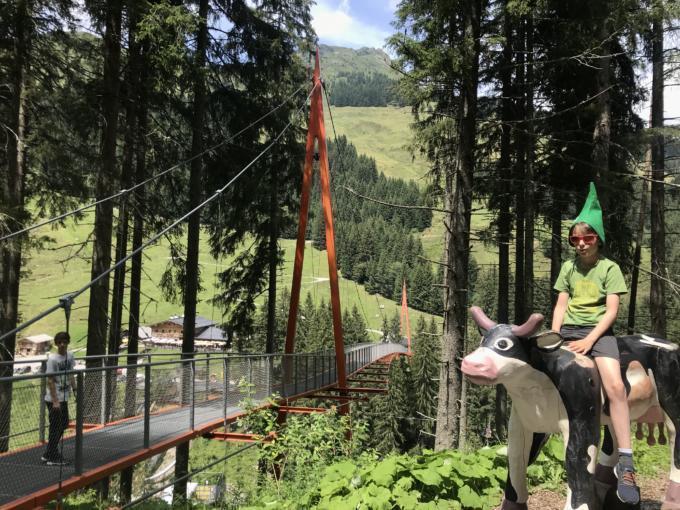 Sie sehen Kinder auf dem Baumzipfelweg in Saalbach spazieren. JUFA Hotels bietet Ihnen den Ort für erlebnisreichen Natururlaub für die ganze Familie.