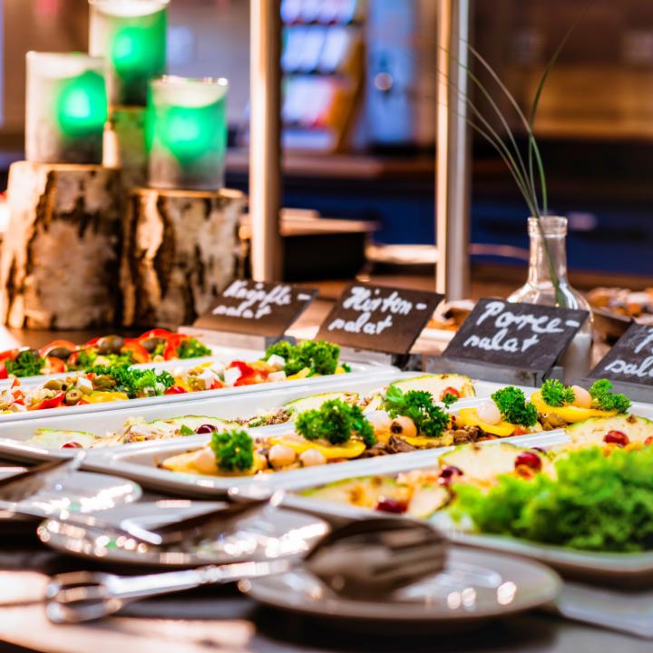 Sie sehen ein Salatbuffet im JUFA Hotel Königswinter/Bonn mit Kerzen. JUFA Hotels bietet erlebnisreichen Städtetrip für die ganze Familie und den idealen Platz für Ihr Seminar.