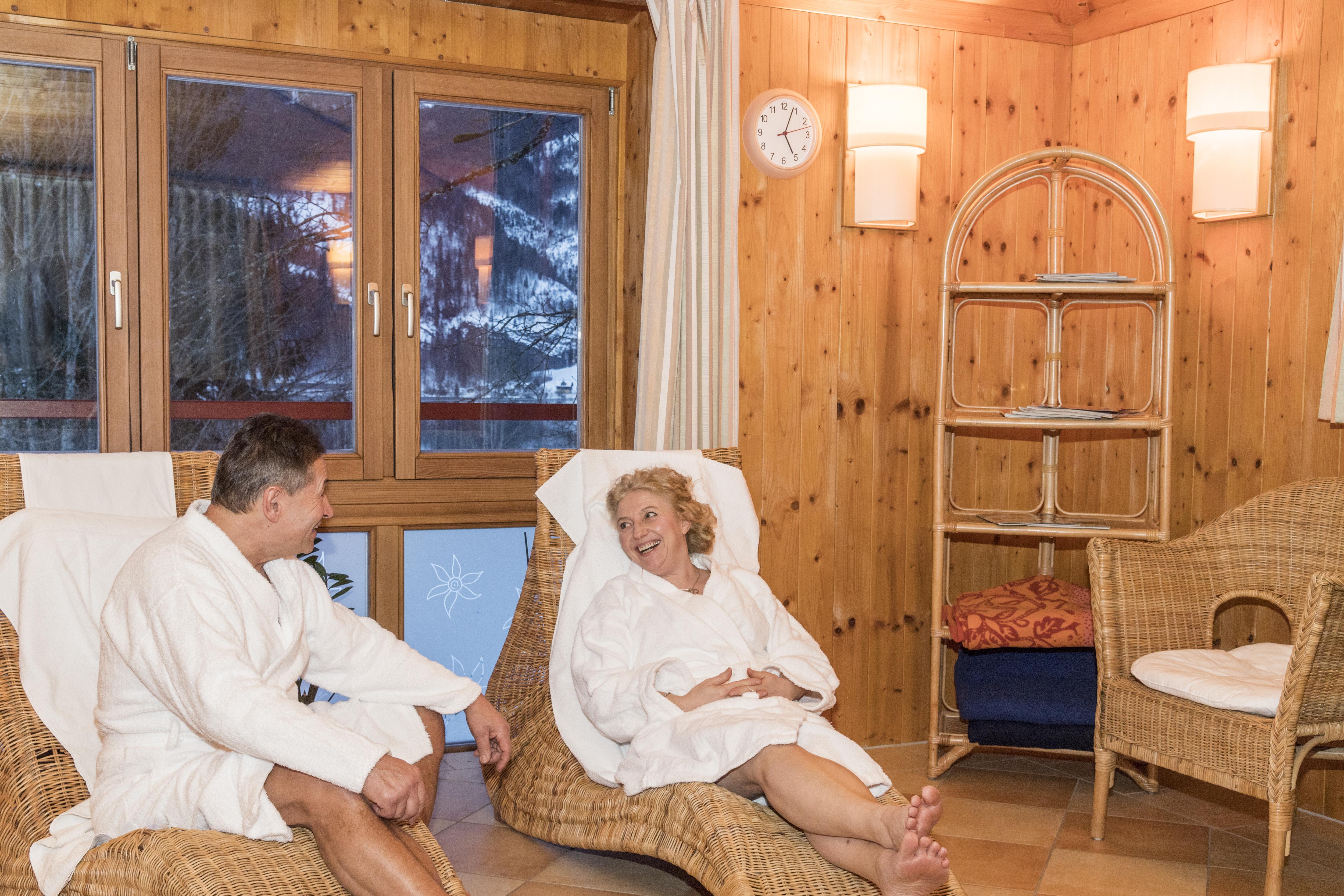 Sie sehen das Sauna-Häuschen im JUFA Hotel Grundlsee*** mit Paar im Winter. JUFA Hotels bietet erholsamen Familienurlaub und einen unvergesslichen Winterurlaub.