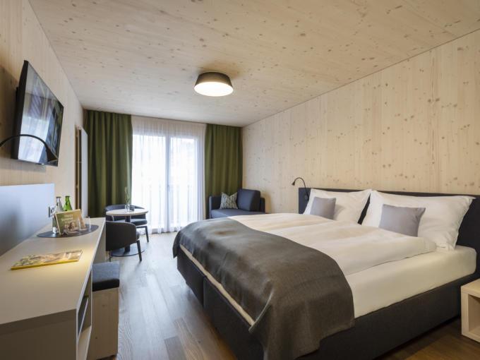 Sie sehen ein FF3 Zimmer im JUFA Hotel Savognin mit ausziehbarer Couch.