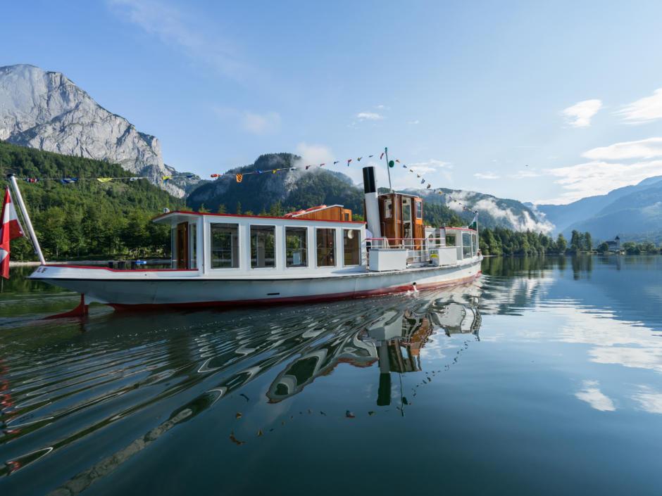 Sie sehen ein Schiff am Grundlsee. JUFA Hotels bietet tollen Sommerurlaub an schönen Seen für die ganze Familie.