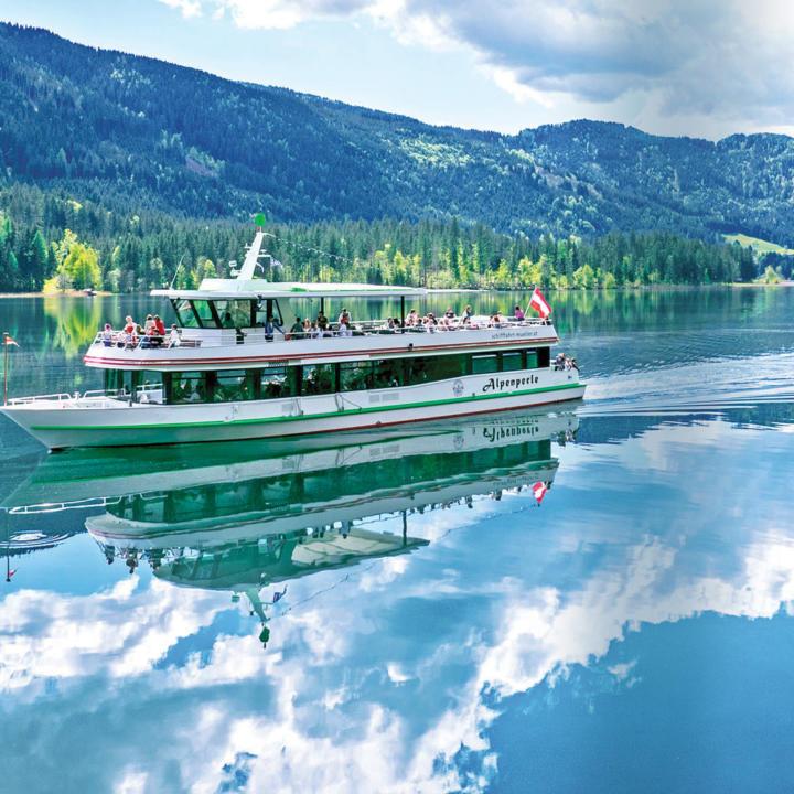 Passagiere machen eine Schifffahrt am Weissensee in Kärnten. JUFA Hotels bieten erholsamen Familienurlaub und einen unvergesslichen Winter- und Wanderurlaub.
