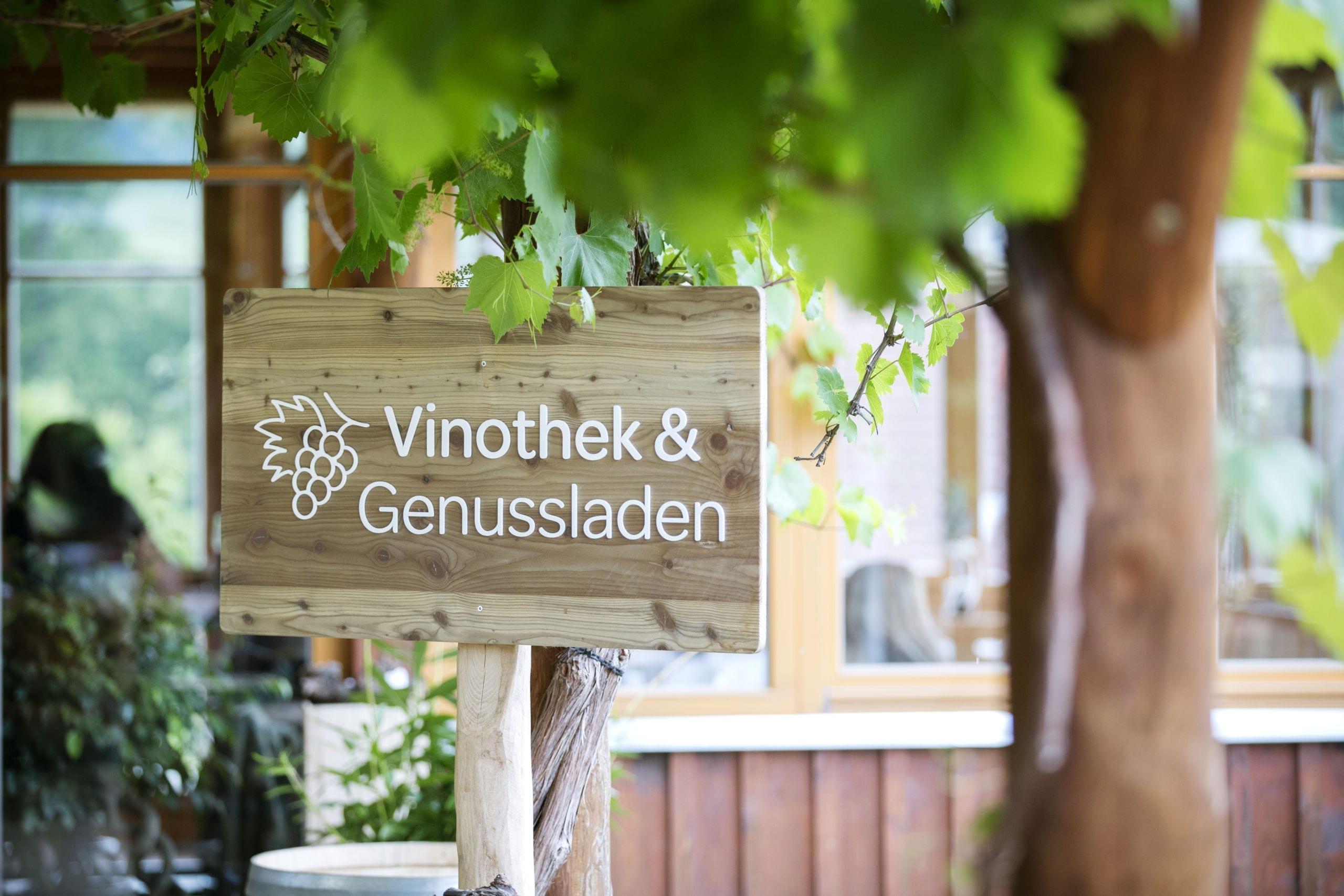 Sie sehen das Schild Vinothek und Genussladen im JUFA Hotel Tieschen – Bio-Landerlebnis. Der Ort für kinderfreundlichen und erlebnisreichen Urlaub für die ganze Familie.