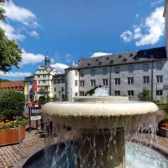 Sie sehen das imposante Schloss Bad Mergentheim mit einem Brunnen im Sommer. JUFA Hotels bietet erholsamen Familienurlaub und einen unvergesslichen Winter- und Wanderurlaub.