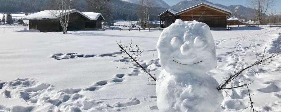 Sie sehen einen Schneemann am Weissensee in Kärnten im Winter. JUFA Hotels bietet erholsamen Familienurlaub und einen unvergesslichen Winterurlaub.