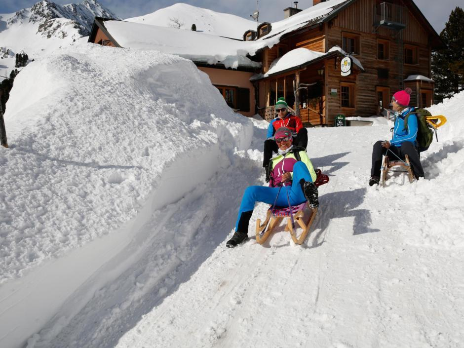 Sie sehen Erwachsene beim Schneeschuhrodeln bei Sonnenschein auf einer Berghütte im Murtal. JUFA Hotels bietet erholsamen Familienurlaub und einen unvergesslichen Winterurlaub.