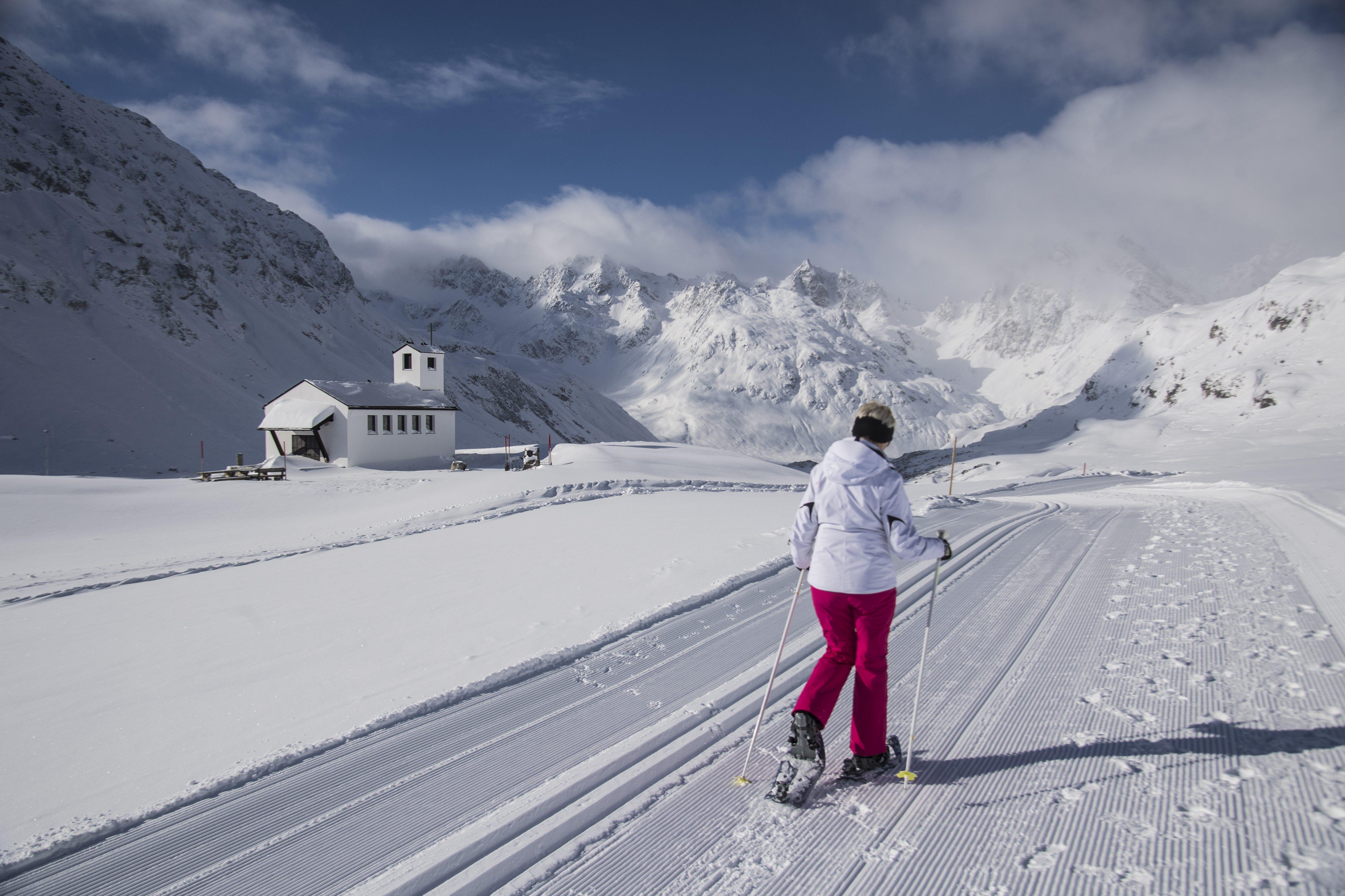 Frau beim Schneeschuhwandern auf einer Loipe am Silvrettasee. In der Nähe des JUFA Hotel Montafon. Der Ort für erholsamen Familienurlaub und einen unvergesslichen Winterurlaub.