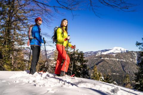 Sie sehen ein Pärchen bei einer Schneeschuhwanderung auf der Mariazeller Bürgeralpe. JUFA Hotels bietet erholsamen Familienurlaub und einen unvergesslichen Winterurlaub.