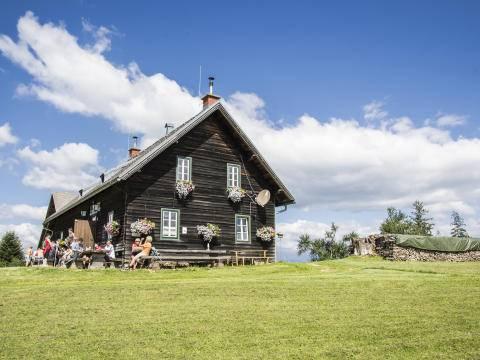 Wanderer genießen die wohlverdiente Jause auf der sonnigen Terrasse des Schutzhauses am Brucker Hochanger im Sommer. JUFA Hotels bietet Ihnen den Ort für erlebnisreichen Natururlaub für die ganze Familie.