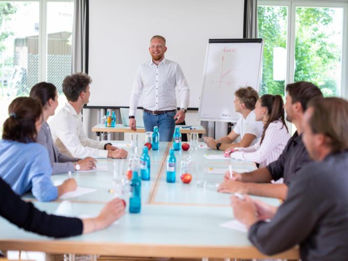 Sie sehen Personen im Vortrag im Seminarraum im JUFA Hotel Nördlingen. Der Ort für kinderfreundlichen und erlebnisreichen Urlaub für die ganze Familie.