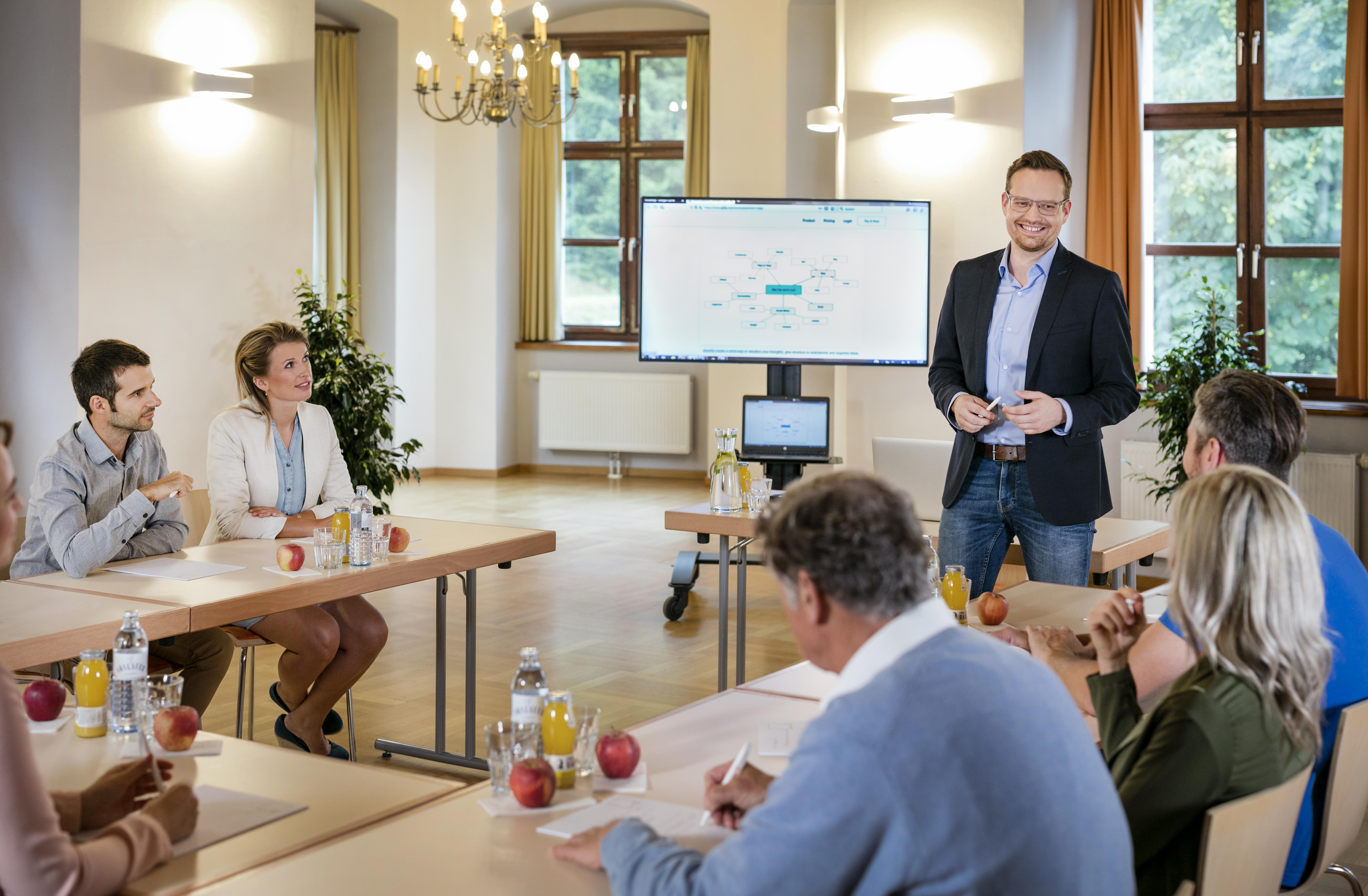 Sie sehen Seminarteilnehmer bei einem Vortrag im JUFA Hotel Schloss Röthelstein/Admont***. Der Ort für märchenhafte Hochzeiten und erfolgreiche und kreative Seminare.