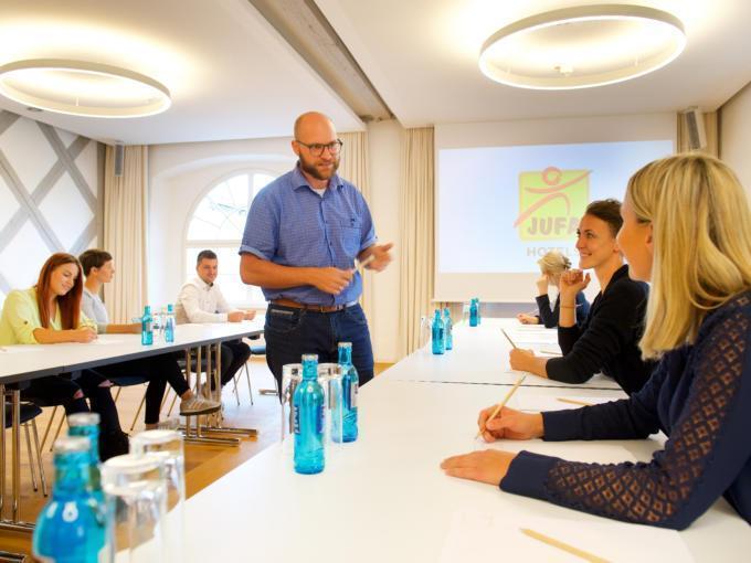Sie sehen einen Vortragenden im Seminarraum des JUFA Hotel Kronach – Festung Rosenberg***. Der Ort für erfolgreiche und kreative Seminare in abwechslungsreichen Regionen.